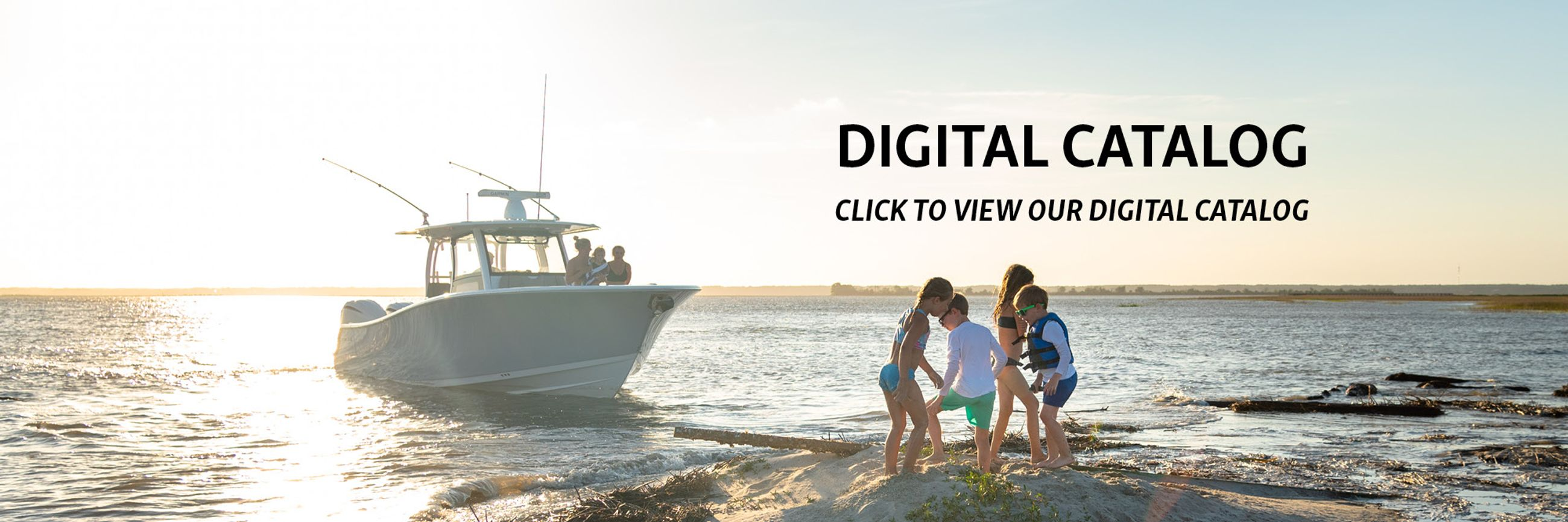Image of kids playing on a sandbar while theres a gray Sportsman boat in the background